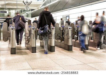 Passengers passing through automatic ticket barriers at underground station - stock photo