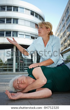 Passerby near helpless senior woman pleading for first aid help - stock photo