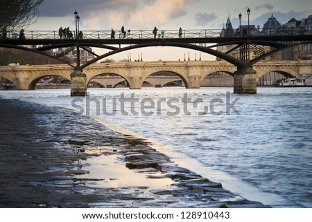 Passerelle des Arts over River Seine in Paris, France. Silhouettes of people walking on it. Pont Neuf (the oldest bridge in Paris) in the distance. - stock photo