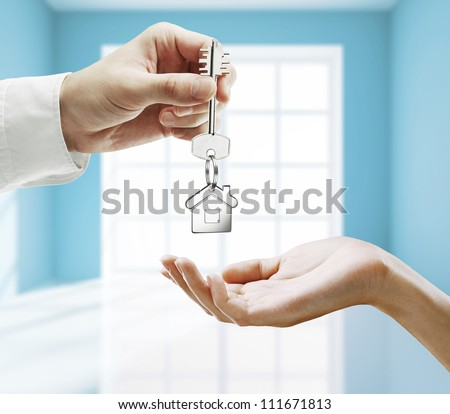 passing key against backdrop of blue room - stock photo