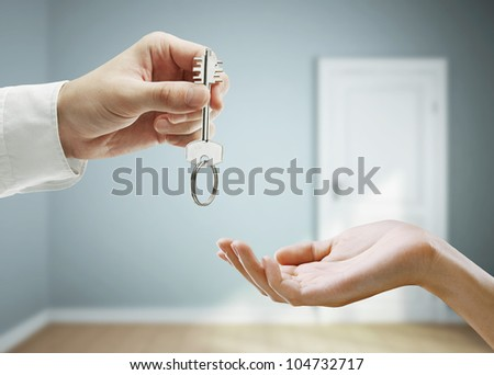 passing keys against the backdrop of blue room - stock photo