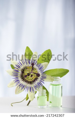 Passion flower with aromatherapy essential oil blue glass - stock photo