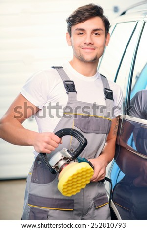 Passionate about cars. Portrait of a handsome car mechanic polishing the luxury car with an orbital polisher and smiling at camera in car repair shop - stock photo