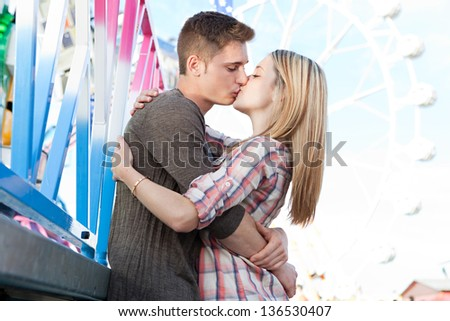 Passionate attractive young couple hugging and kissing while visiting a funfair amusement park arcade, with a ferris wheel in the background. - stock photo