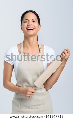 Passionate baker chef in apron holding a rolling pin - stock photo