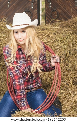 Passionate Caucasian Cowgirl With Lasso Rope in Farm. Vertical Image - stock photo