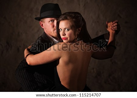 Passionate Caucasian tango partners in 1920s style outfit - stock photo