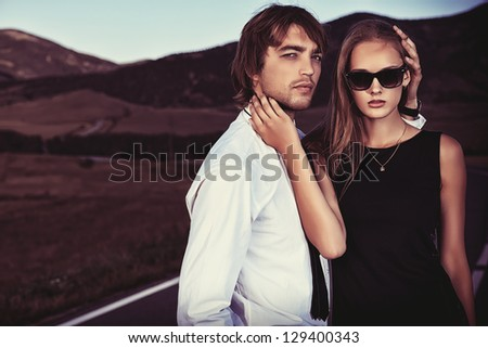 Passionate couple of young people posing on a road over picturesque landscape. - stock photo