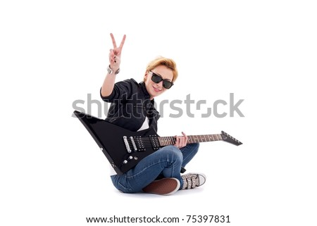 passionate rock girl playing an electric guitar, sitting and making a rock sign - stock photo