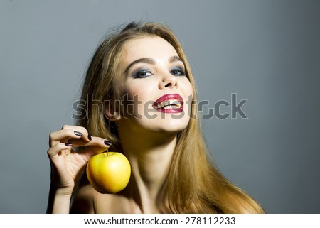 Passionate smiling blonde young woman with bright make up looking forward holding fresh yellow apple standing on gray background copyspace, horizontal picture - stock photo