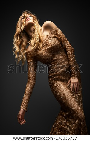 Passionate woman in a brown dress on gray background - stock photo