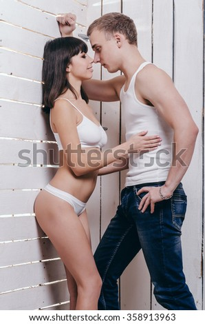 Passionate young couple hugging near a wall. Woman in underwear. - stock photo