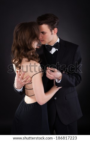 Passionate young man removing dress strap from woman's shoulder isolated over black background - stock photo