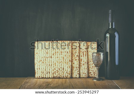 Passover background. wine and matzoh (jewish holiday bread) image is filtered with retro faded style - stock photo