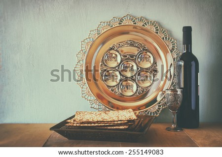 Passover background. wine and matzoh (jewish passover bread) over wooden background. image is retro filtered with faded style - stock photo