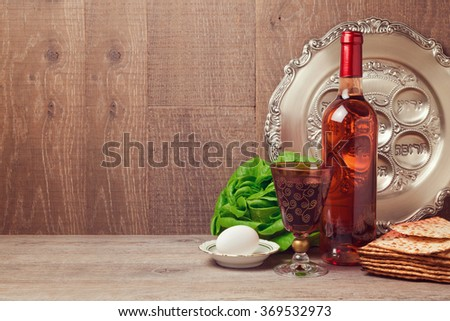 Passover background with wine bottle, matzoh, egg  and seder plate - stock photo