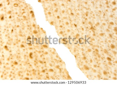 Passover broken matzah. Closeup of matzah broken into two pieces. One piece will be the afikoman for the seder meal. Isolated on a white background. - stock photo
