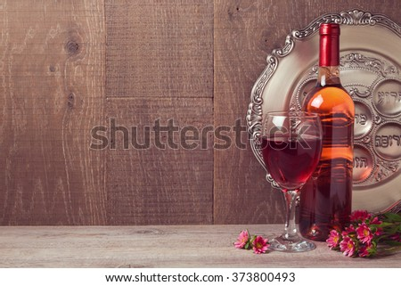 Passover celebration with wine and seder plate over wooden background - stock photo