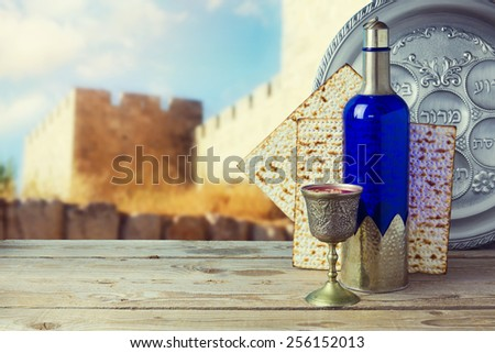 Passover matzo and wine on wooden vintage table over old city walls. Seder plate with hebrew text says bone and  lettuce. - stock photo
