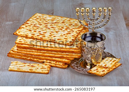 passover matzo (jewish passover bread) with kiddush cup of wine on wooden table - stock photo