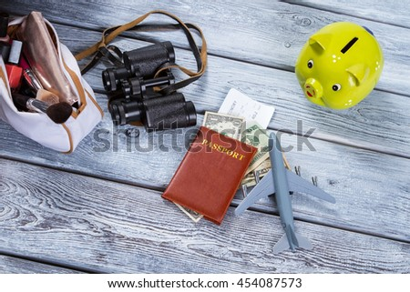 Passport and a toy plane. Lime piggy bank and binoculars. Run away from the bustle. Take a vacation this summer. - stock photo