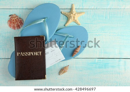 passport and ticket with beach shoes on a blue wooden background with different types of seashells - stock photo