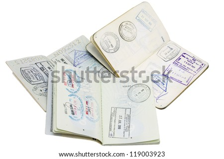 Passport Stamps/ three passports opened at stamped pages - stock photo