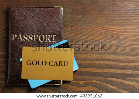 passport with a gold credit card on a brown wooden background - stock photo