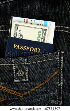passport with boarding pass and money in black jeans back pocket - stock photo