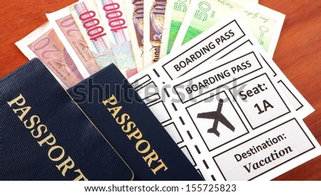 Passports with airline boarding pass and foreign currency - stock photo