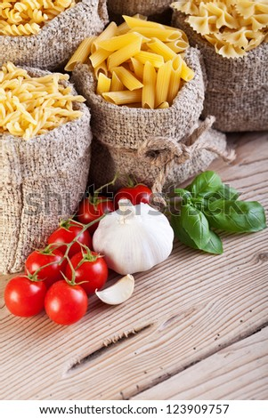 Pasta and cooking ingredients - traditional food setting - stock photo