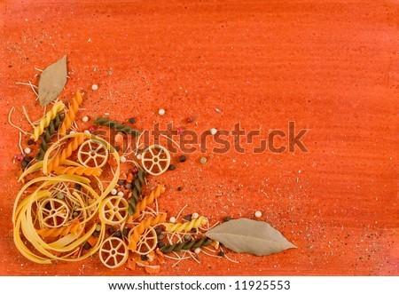 Pasta and spices on orange background - stock photo