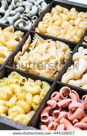 pasta assortment background. Pasta in a wooden box. Italian pasta of different colors. focus on the paste in the upper portion of the frame - stock photo