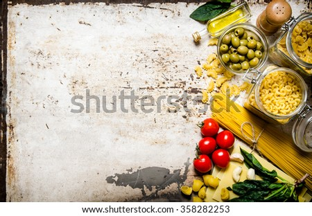 Pasta background. A lot of different pasta, olives, tomatoes, oil and herbs. On rustic background.  Free space for text . Top view - stock photo