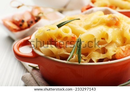 Pasta baked with shrimps and cheese in ceramic pot - stock photo