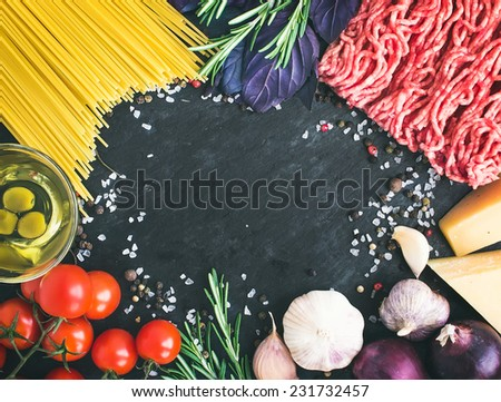 Pasta Bolognese ingredients: spaghetti, minced meat, tomatoes, basil, rosemary, parmesan, olive oil, garlic, onion, sea salt and spices on a dark stone background with a copy space in the center - stock photo