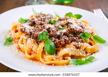 Pasta Bolognese with parmesan and basil on table close up - stock photo
