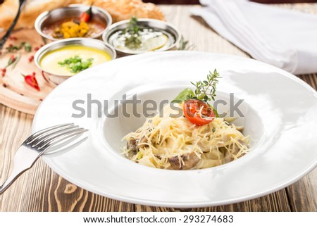 Pasta carbonara with mushroom and sauce on wooden background. Top view - stock photo