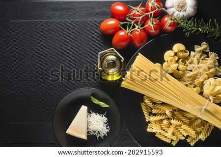 Pasta collection and fresh ingredients on a black background overhead shoot - stock photo