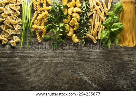 Pasta collection with herbs on rustic wooden background - stock photo