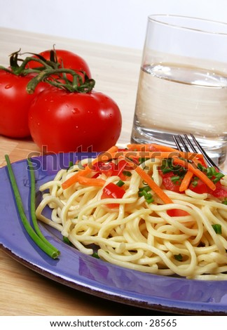 pasta dinner plate with noodles, tomato, carrots, and chives. - stock photo