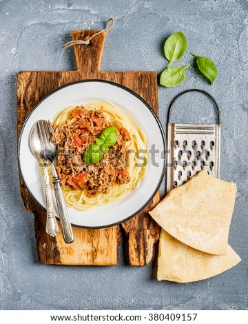 Pasta dinner. Spaghetti Bolognese in metal plate on rustic wooden board with Parmesan cheese, grater and fresh basil on grey concrete background, top view - stock photo