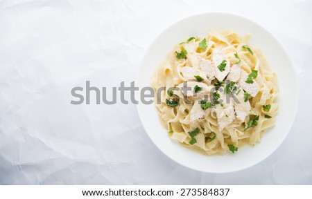 Pasta fettuccine alfredo with chicken, parmesan and parsley on white textured background top view. Italian cuisine. Space for text. - stock photo