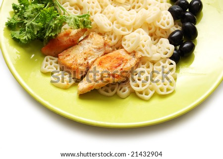 Pasta, fried chiken , olives and parsley on green plate - stock photo