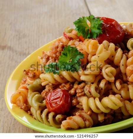 Pasta fusilli with bolognese tomato beef sauce on the kitchen table - stock photo