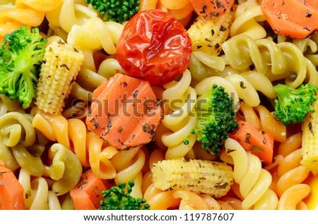 Pasta fusilli with broccoli, carrot, corn, and tomatoes - stock photo