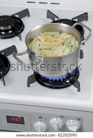 Pasta in a pot on the gas stove. - stock photo