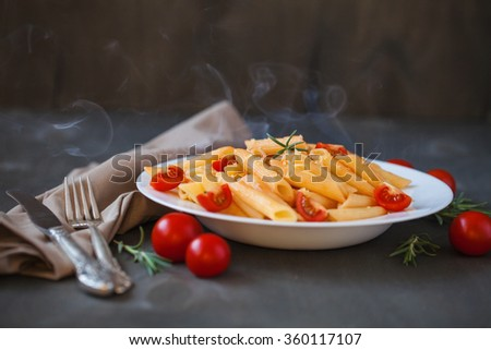 Pasta in tomato sauce on a wooden table - stock photo