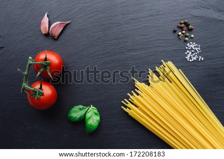 Pasta ingredients concept on black slate background viewed from the top - stock photo