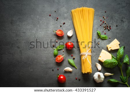 Pasta ingredients. Ingredients for cooking Italian pasta - spaghetti, tomatoes, basil, oil and garlic. Italian food. Top view with space for text. - stock photo